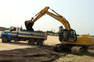 Picture of an Excavator putting mud in a dump truck clearing a site